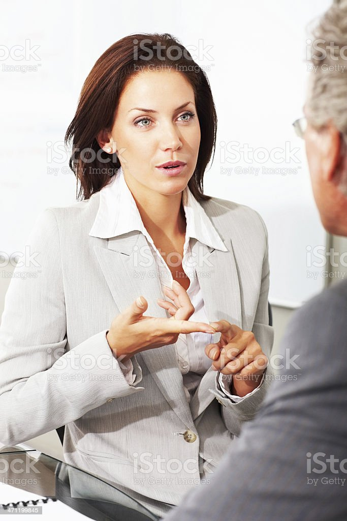 Businesswoman discussing with her colleague royalty-free stock photo