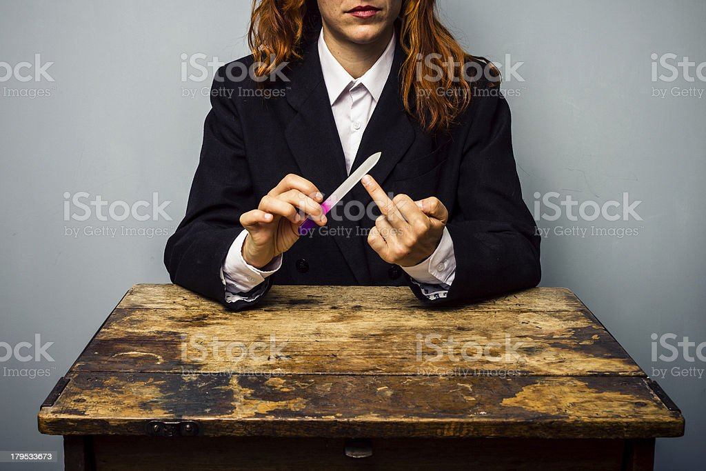 Businesswoman displaying obscene gesture while filing her nails stock photo