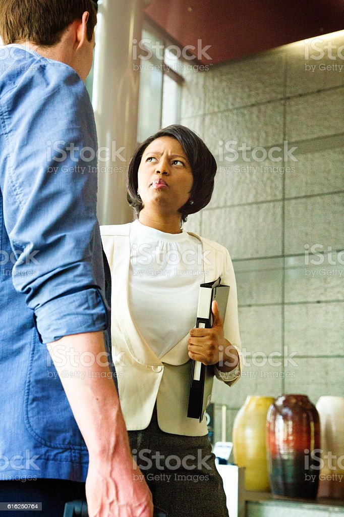 Businesswoman distraught by pre-meeting briefing in lobby stock photo