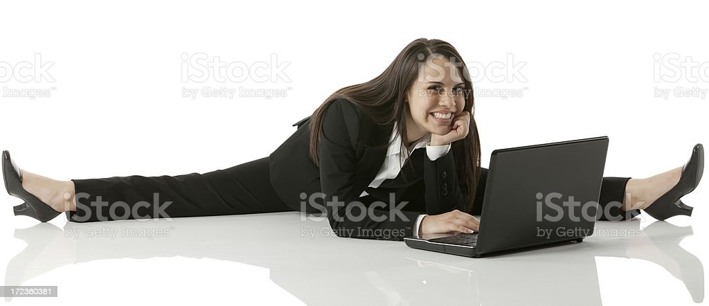 Businesswoman doing a split and using laptop royalty-free stock photo