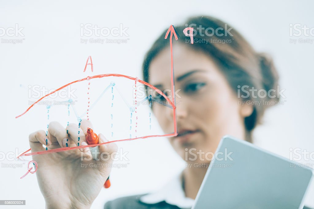 Businesswoman drawing a chart on transparent board stock photo