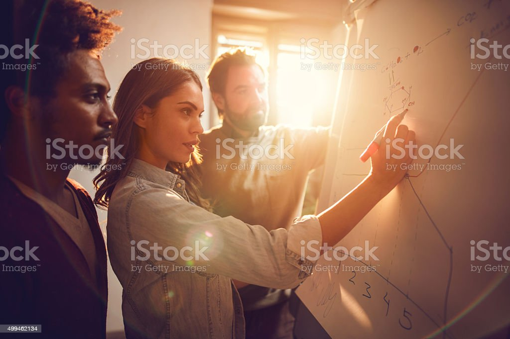 Businesswoman drawing a graph together with her two male colleagues. stock photo