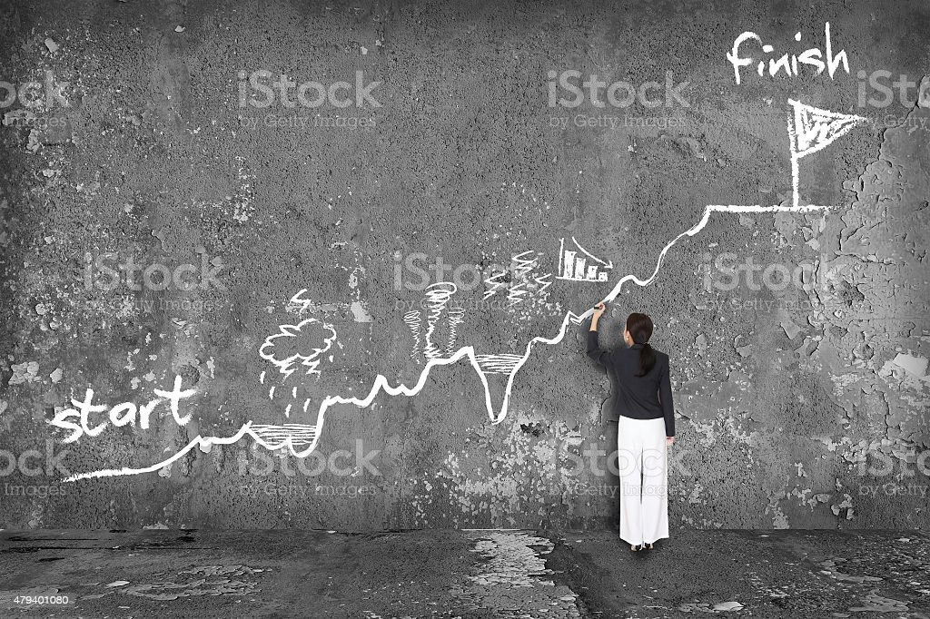 businesswoman drawing a way to success on the wall stock photo