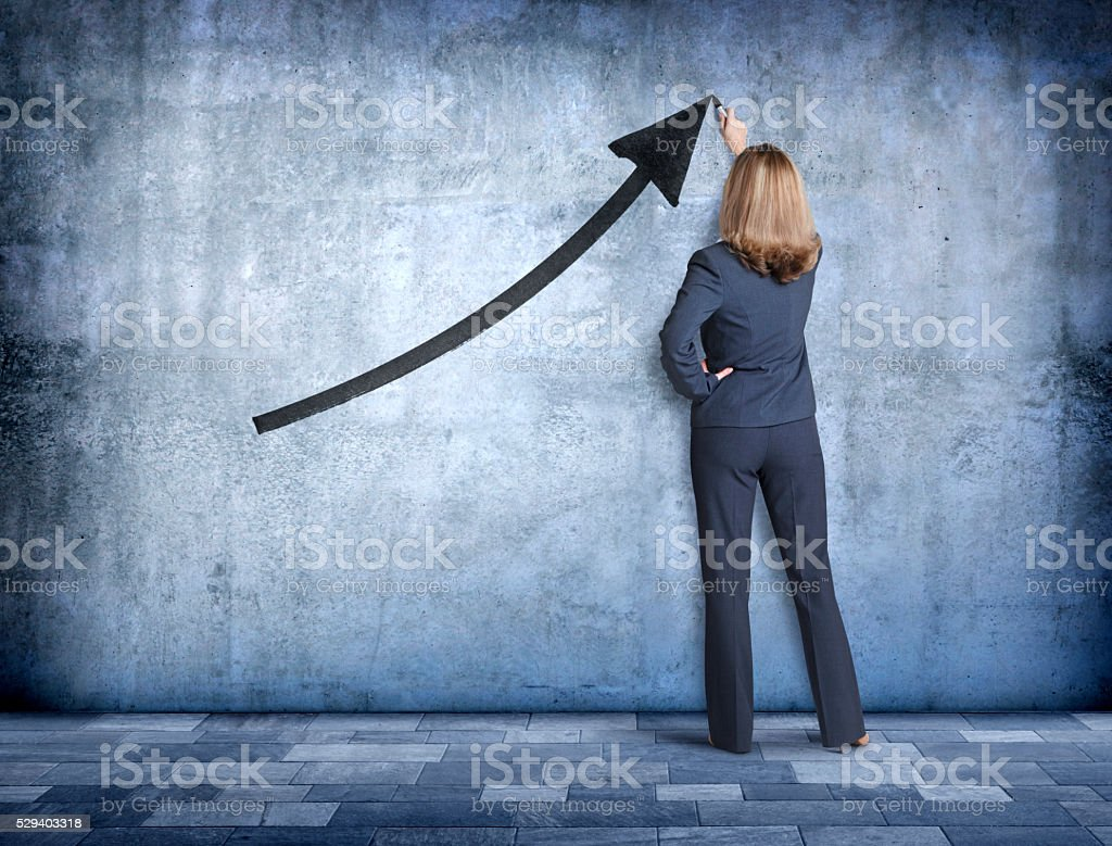Businesswoman Drawing An Upward Pointing Arrow On Concrete Wall stock photo