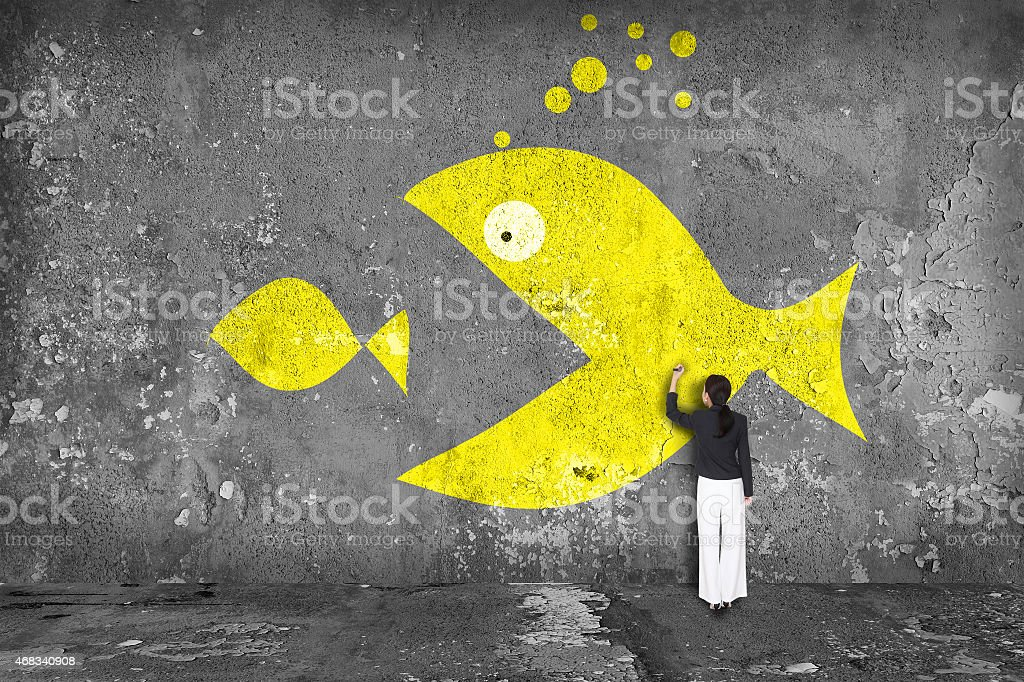 businesswoman drawing  big fish  on the wall stock photo