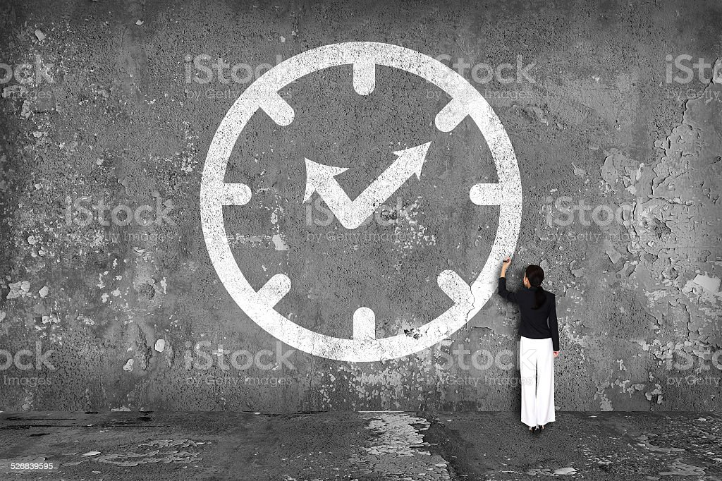 businesswoman drawing  clock on the wall stock photo