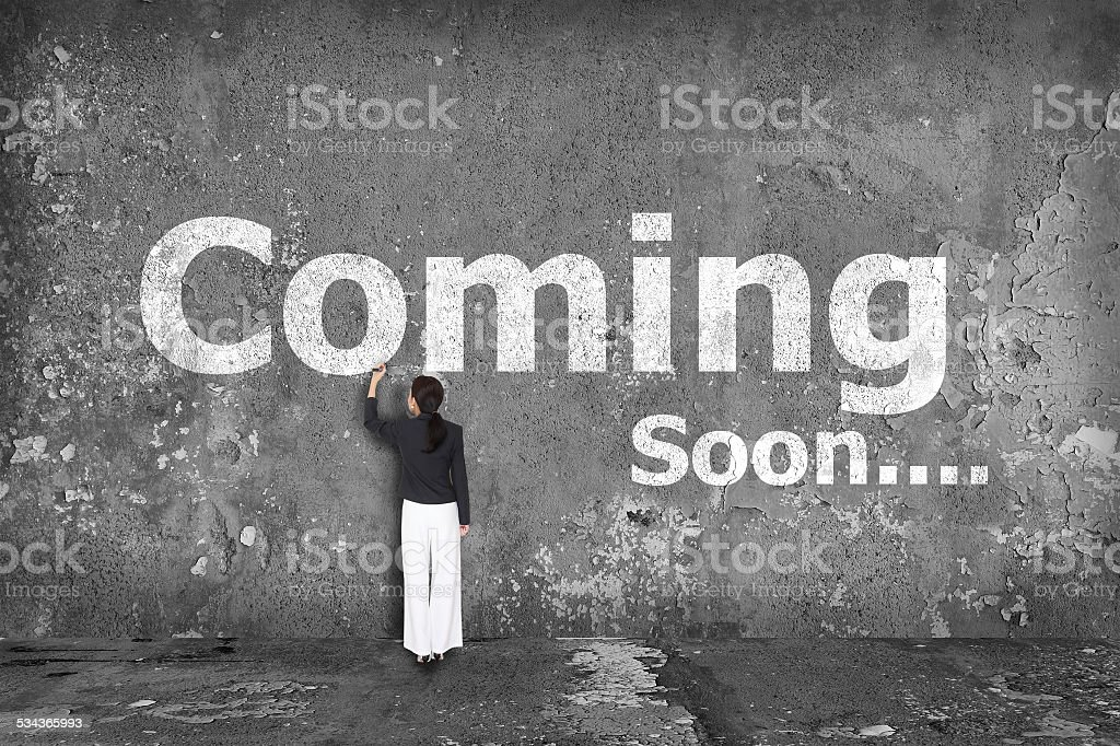 businesswoman drawing coming soon on wall stock photo