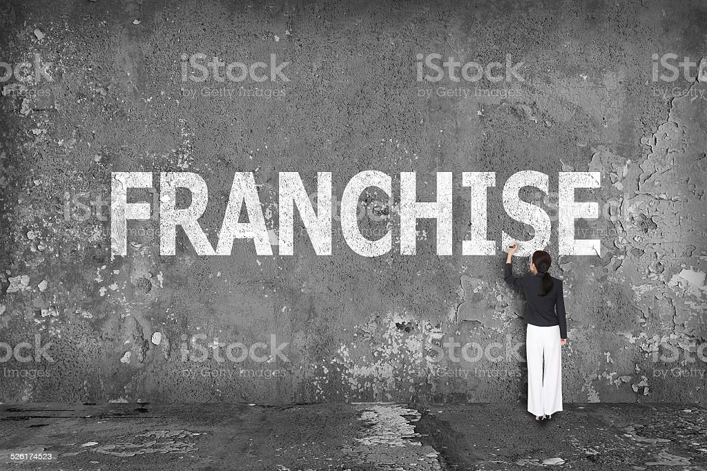 businesswoman drawing franchise on the wall stock photo