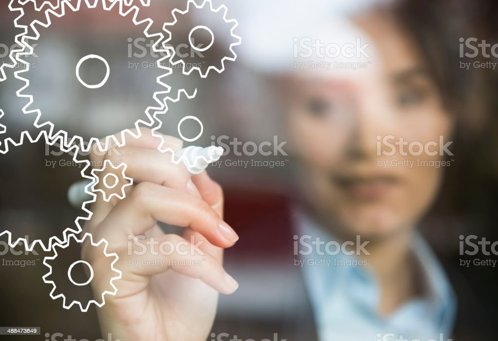 Businesswoman drawing gears stock photo