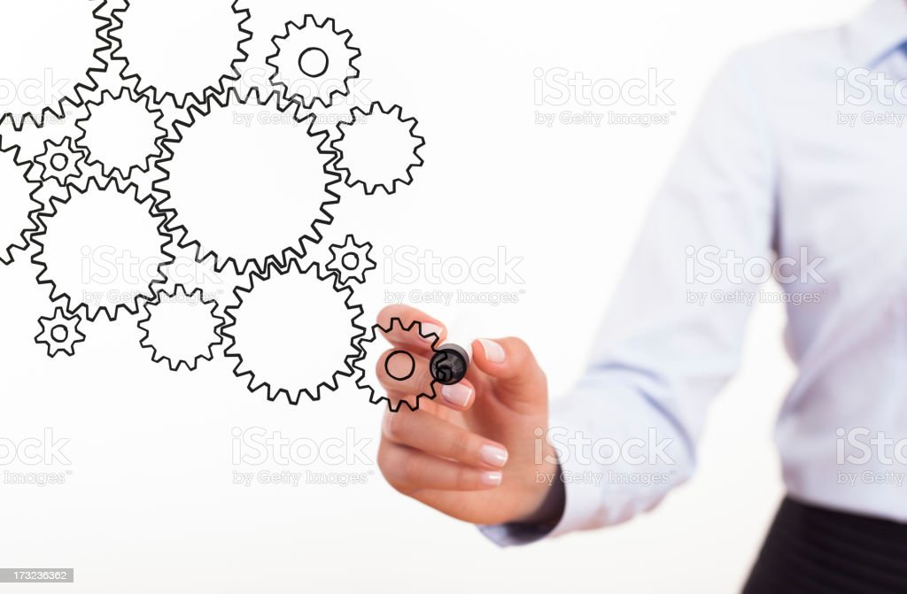 Businesswoman drawing group of gears on screen stock photo