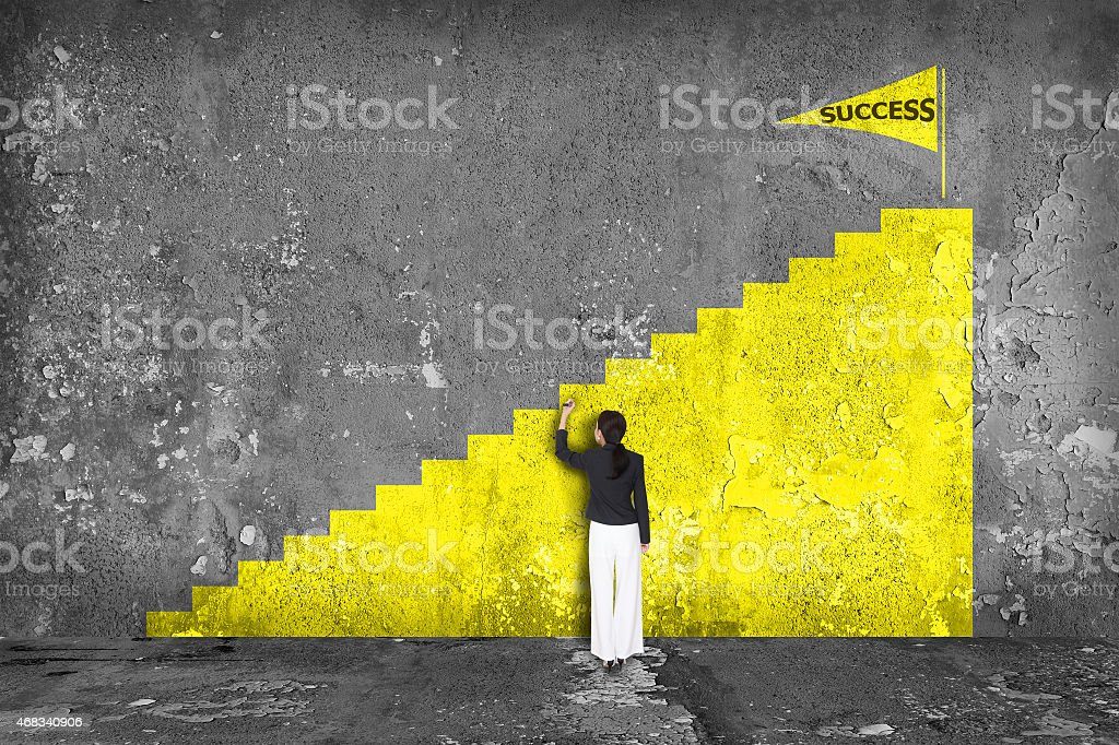 businesswoman drawing  ladder of success on the wall stock photo