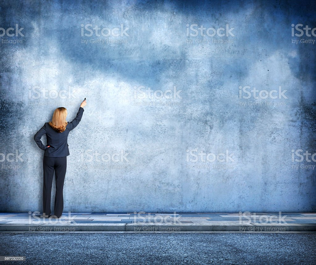 Businesswoman Drawing On A Blank Wall stock photo