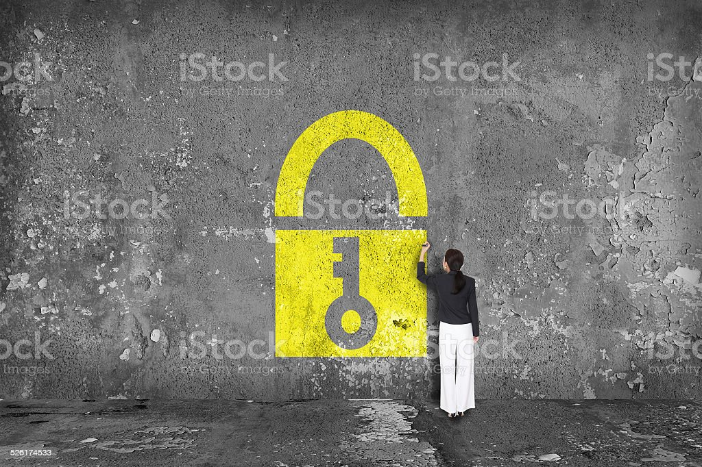 businesswoman drawing padlock on the wall stock photo
