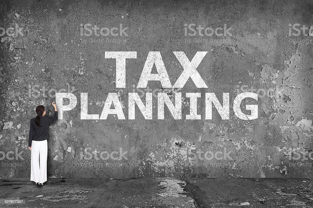 businesswoman drawing tax planning on the wall stock photo