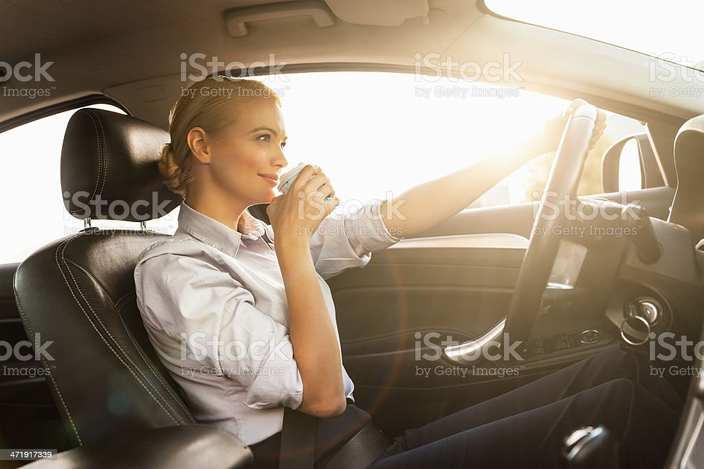 Businesswoman dringking cofee while driving stock photo
