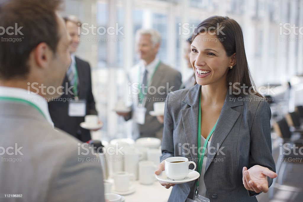 Businesswoman drinking coffee and talking to co-worker stock photo