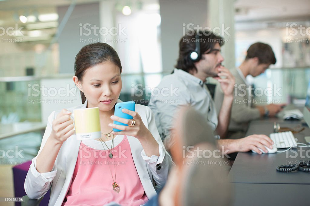 Businesswoman drinking coffee and text messaging with feet up in office stock photo
