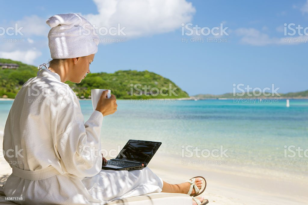businesswoman drinking coffee and working on laptop at a beach royalty-free stock photo