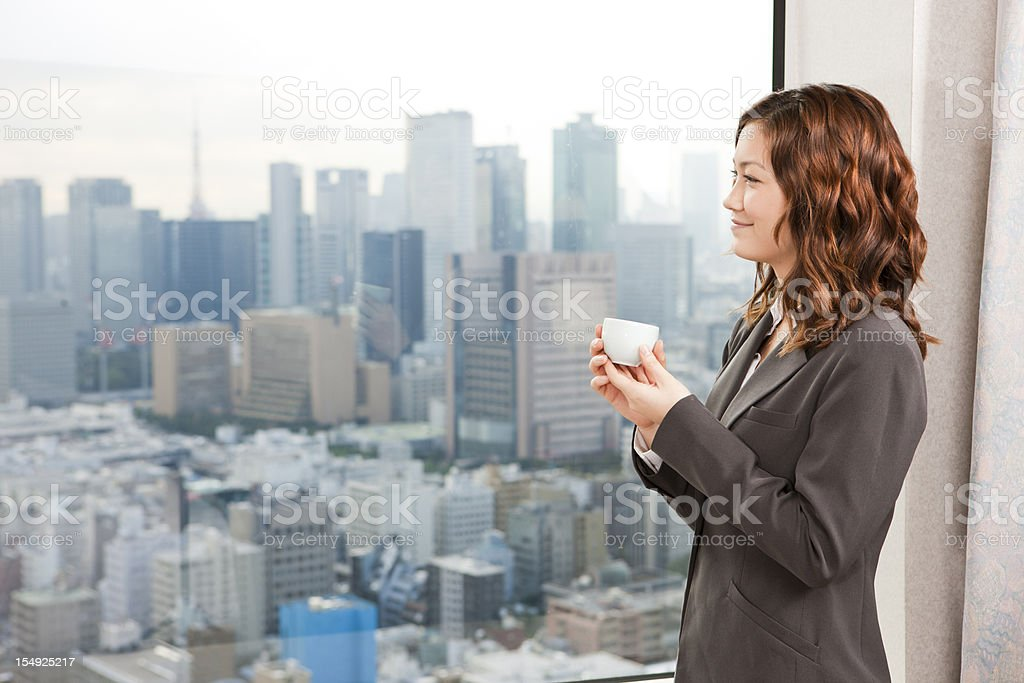 Businesswoman drinking coffee while looking at cityscape royalty-free stock photo