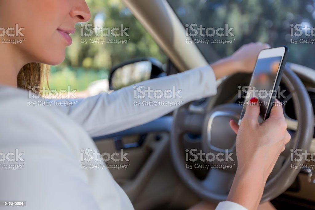 Businesswoman driving and looking at phone stock photo