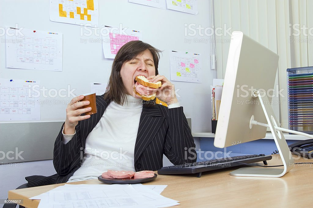 Businesswoman eating a sandwich by her desk royalty-free stock photo