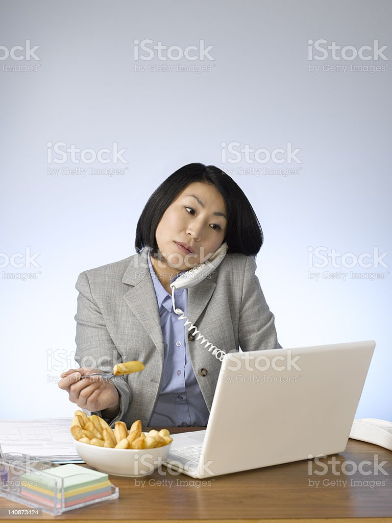 Businesswoman eating and working at desk stock photo