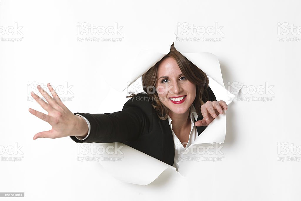Businesswoman emerging through ripped out hole royalty-free stock photo