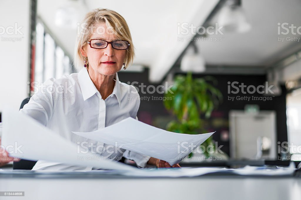Businesswoman examining documents at desk stock photo