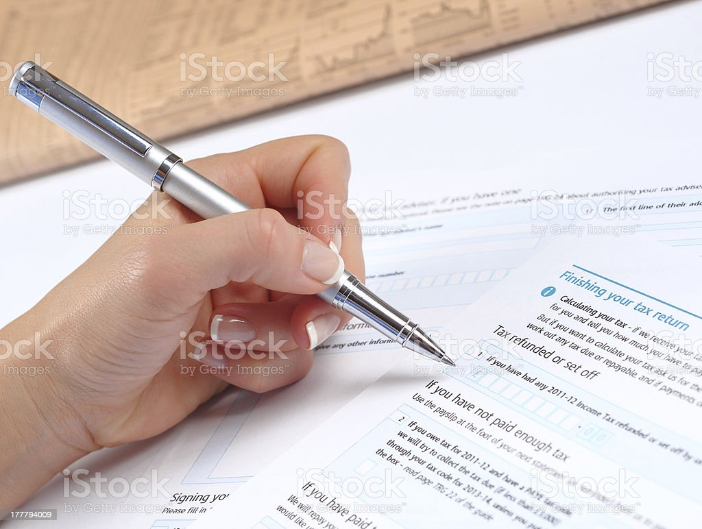 Businesswoman filling blank UK tax form in accounting office royalty-free stock photo