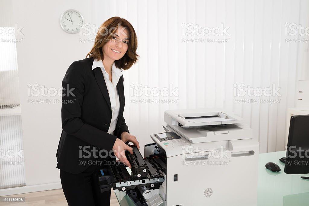 Businesswoman Fixing Copy Machine stock photo