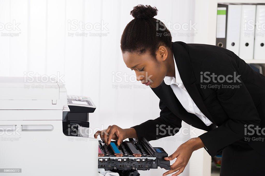 Businesswoman Fixing Photocopy Machine stock photo