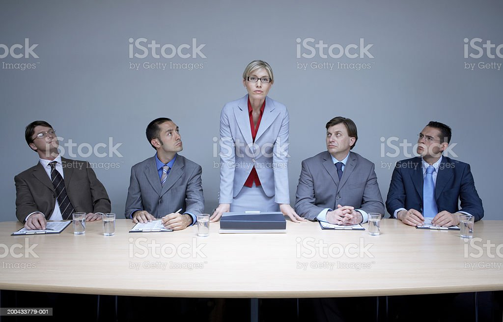 Businesswoman flanked by businessmen standing up from boardroom table stock photo