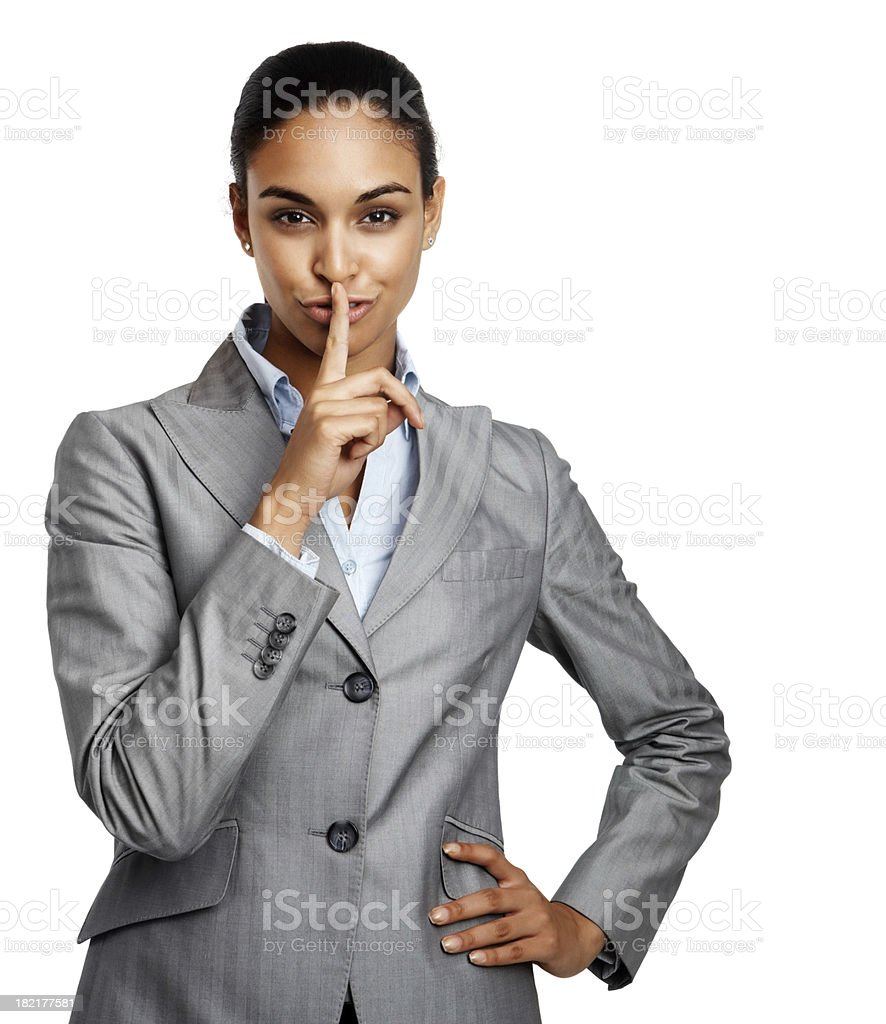 Businesswoman gesturing with finger on lips royalty-free stock photo