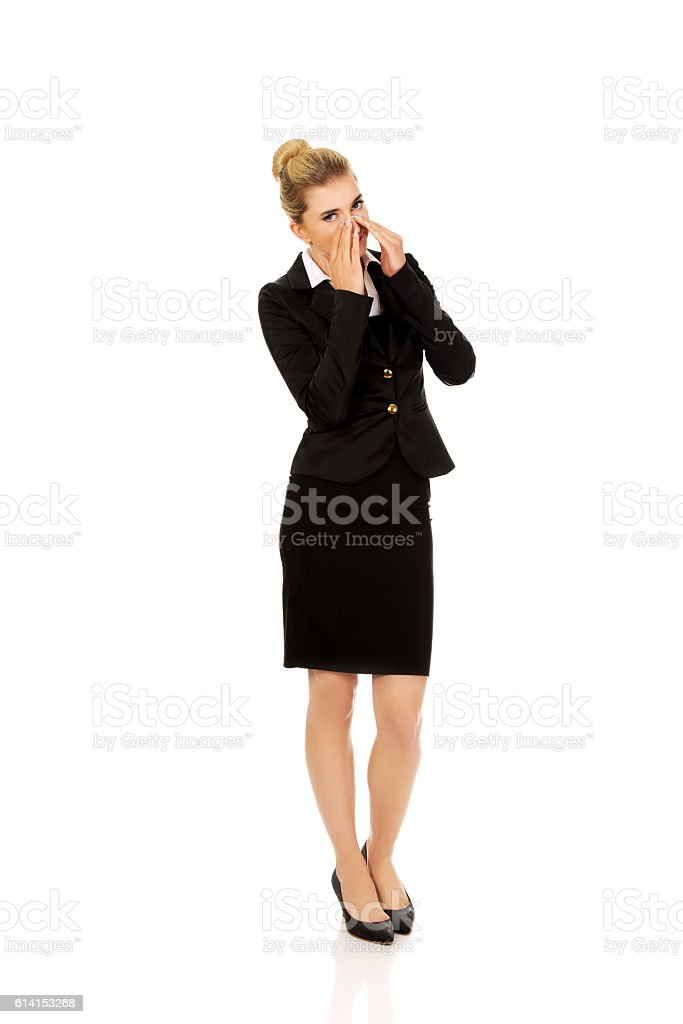 Businesswoman giggles covering her mouth with hand stock photo