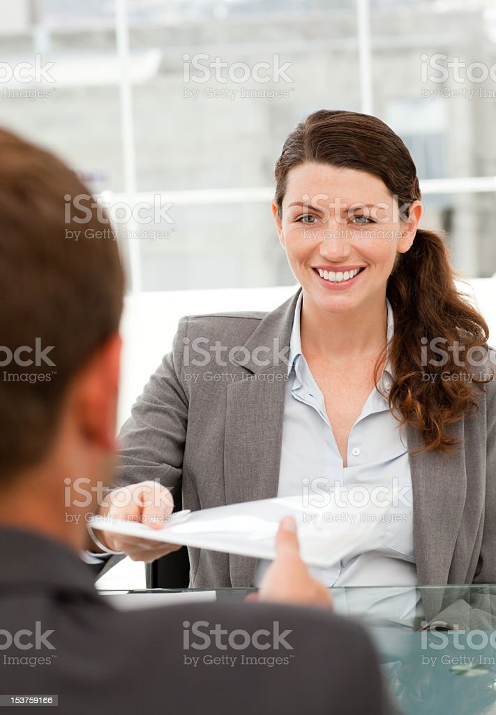 Businesswoman giving documents to a colleague royalty-free stock photo