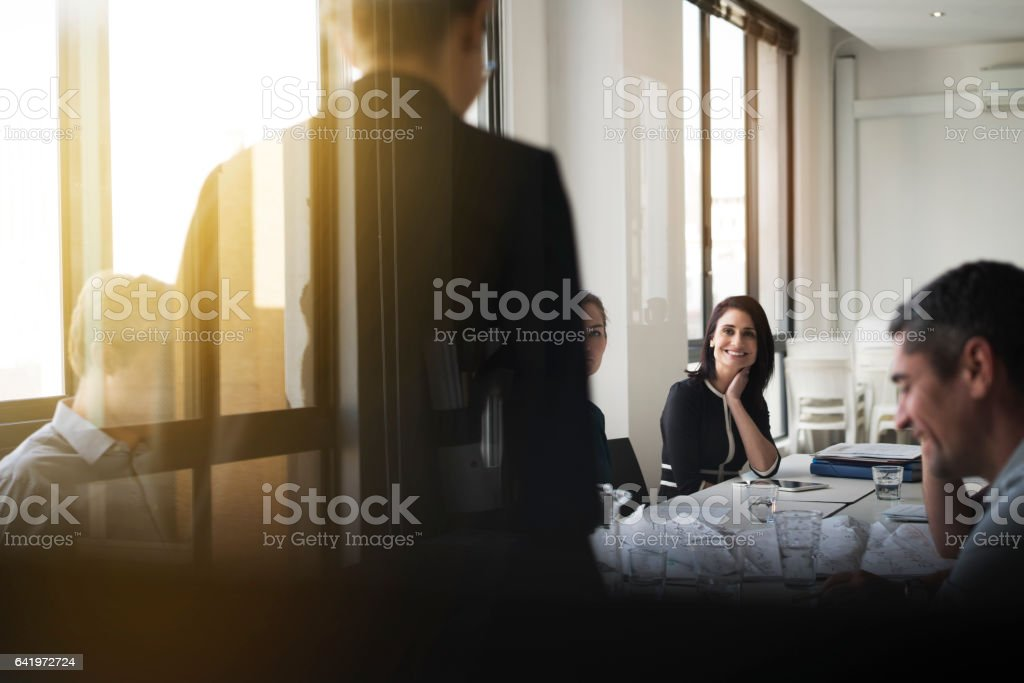 Businesswoman giving presentation in board room stock photo