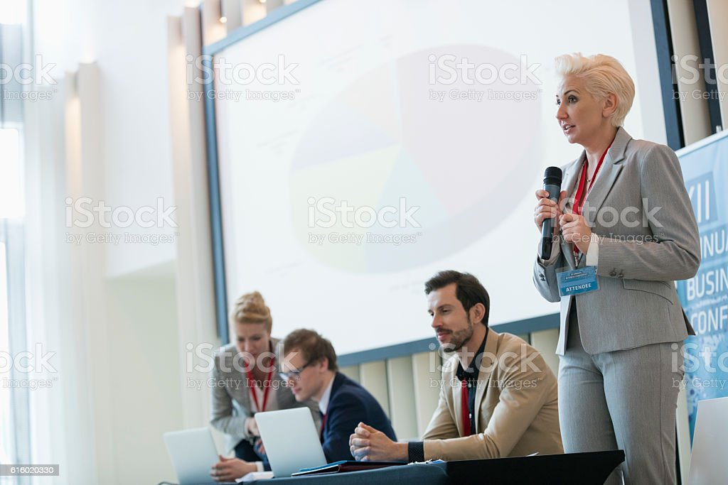 Businesswoman giving presentation in seminar hall stock photo