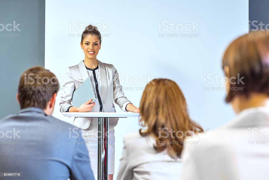 Businesswoman giving presentation to his colleagues stock photo