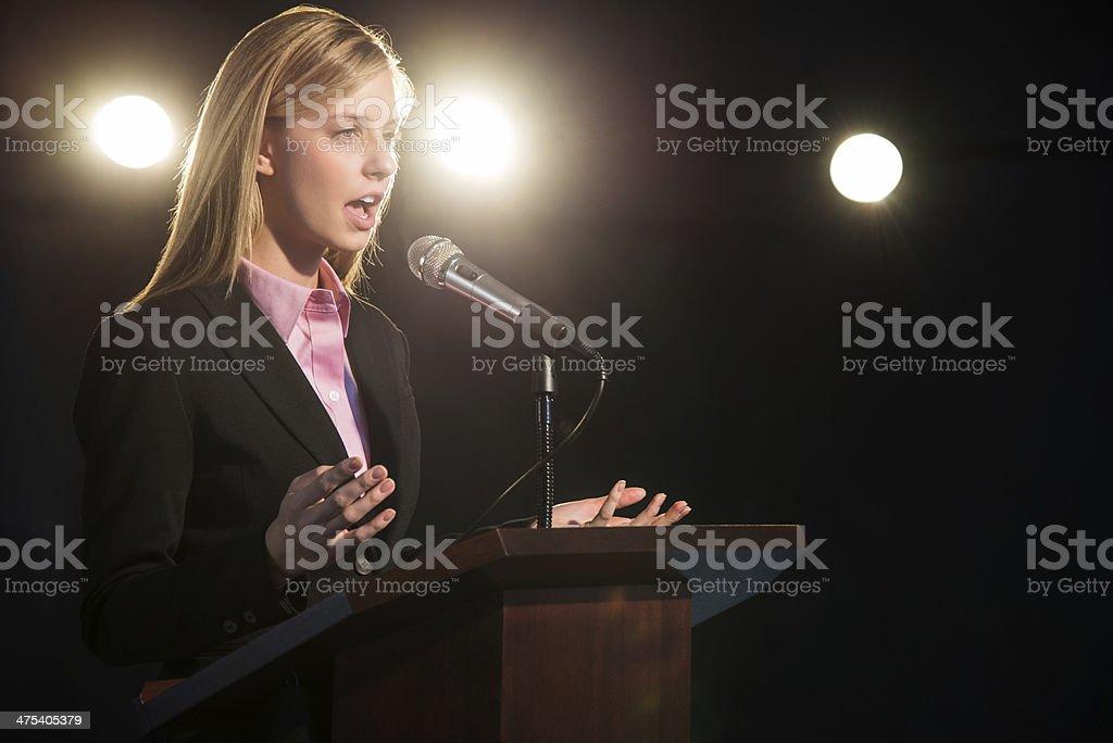 Businesswoman Giving Speech At Podium In Auditorium stock photo