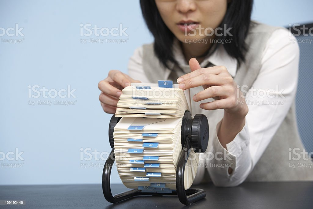 Businesswoman Going Through Rotary Card File stock photo