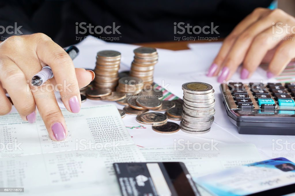 businesswoman hand counting on saving account with stack of coins stock photo