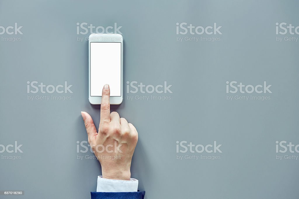 Businesswoman hand touching smartphone on gray table stock photo