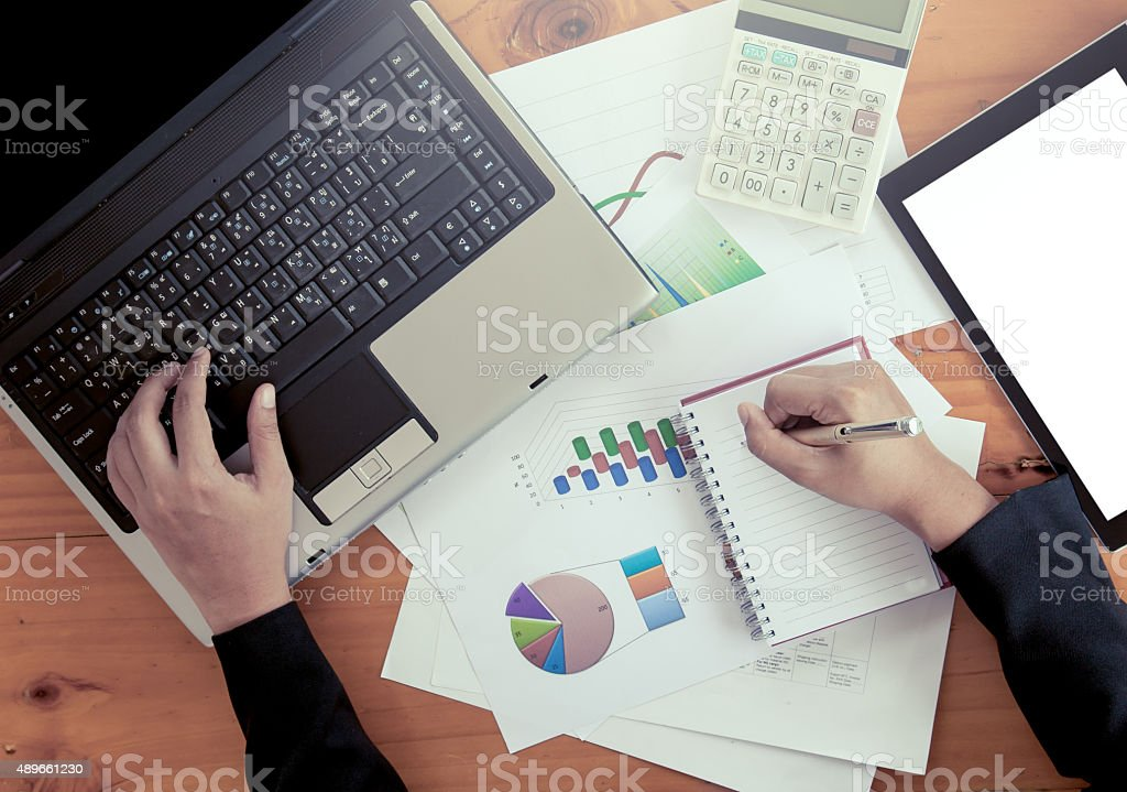 Businesswoman hand writing on notebook and typing on laptop keyb stock photo
