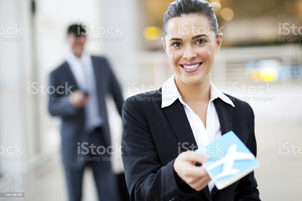businesswoman handing over air ticket at check in counter stock photo