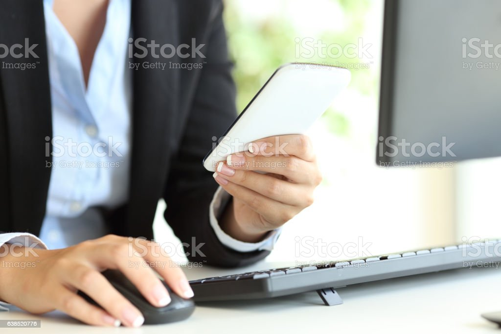 Businesswoman hands using a pc mouse and phone stock photo