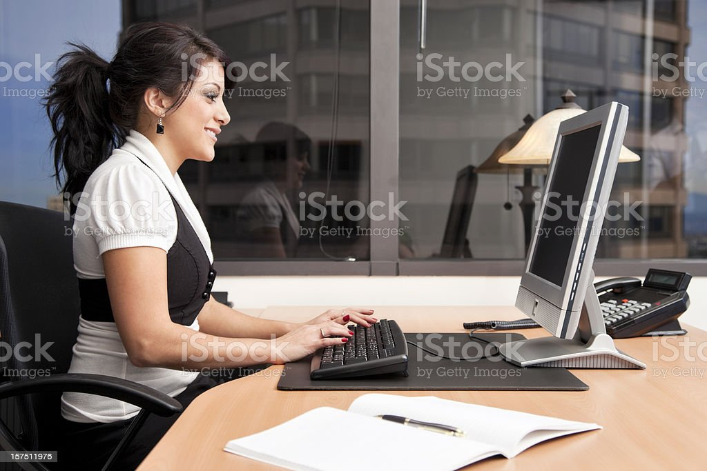 Businesswoman Happily Working at Her Desk royalty-free stock photo