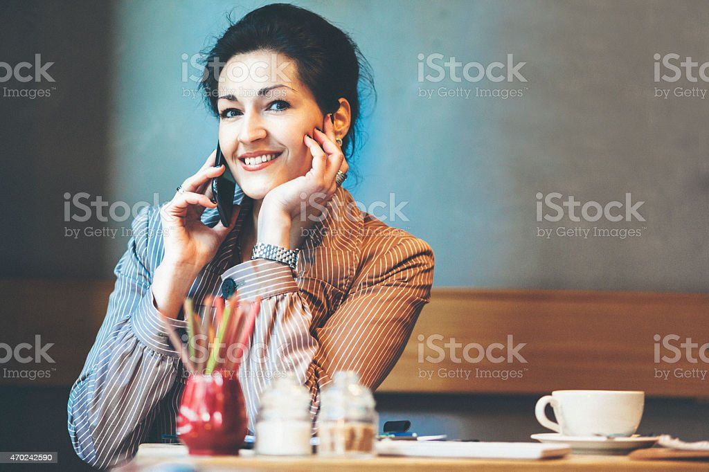 Businesswoman having a coffee break and talking on the phone stock photo