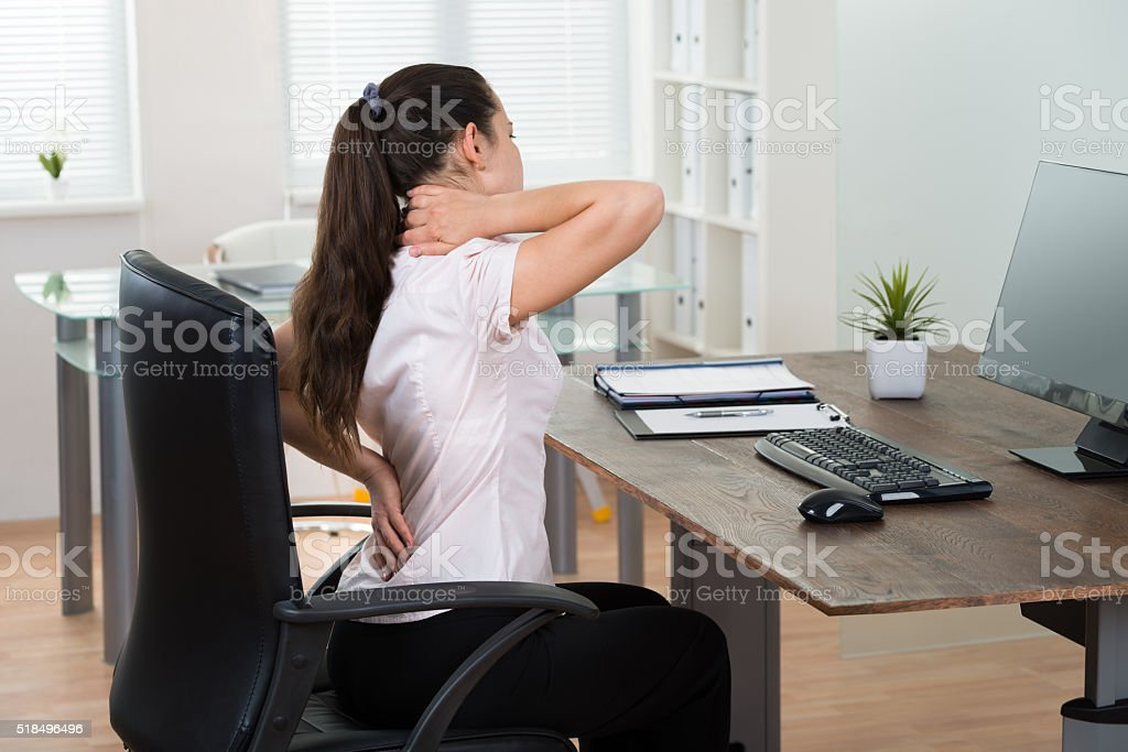 Businesswoman Having Backpain In Office stock photo