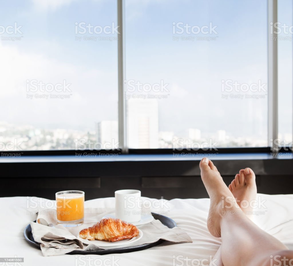 Businesswoman having breakfast in bed stock photo
