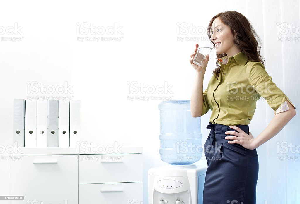 Businesswoman having drink from Water cooler. royalty-free stock photo